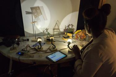 A woman arranges items on a table and uses an iPad to control lights.