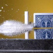 A playing card being split with a bullet
