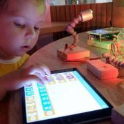 A boy works with an iPad.