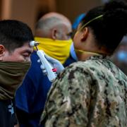 Sailors assigned to the aircraft carrier USS Theodore Roosevelt are checked for body temperature amid the coronavirus pandemic at Naval Base Guam, United States on April 07, 2020.