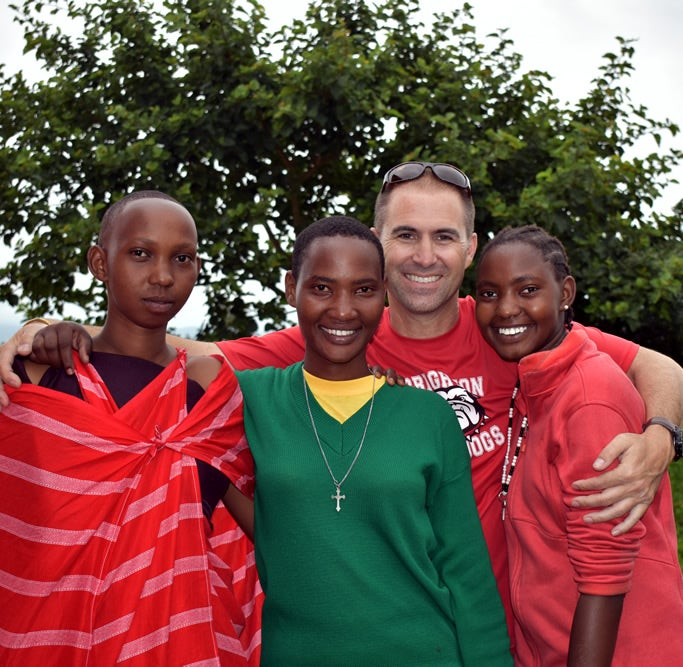 Tony Matteroli, who adopted Mollel in 2014, poses with Mollel and two of her sisters.