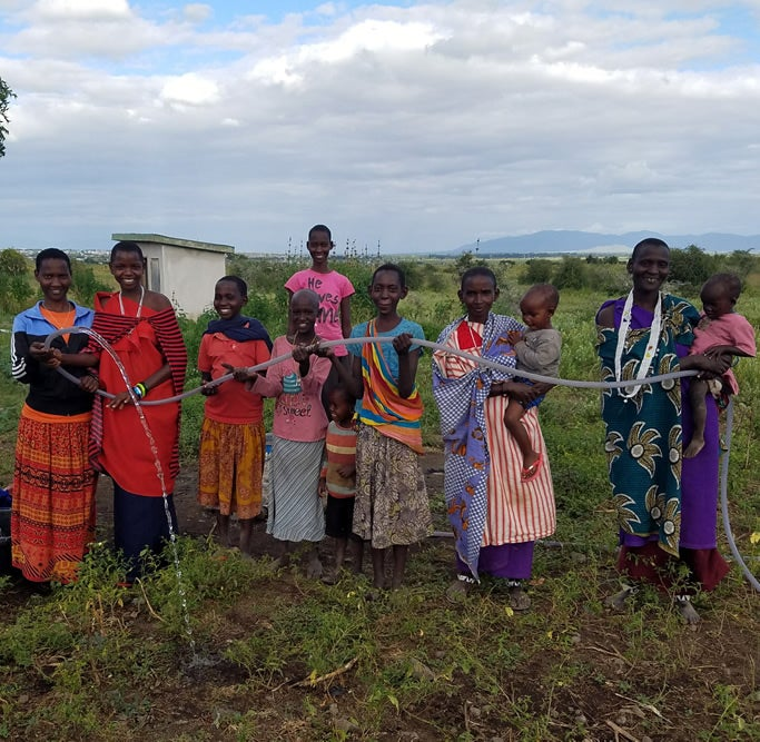 Maasai people show off their new water supply in 2015, one of Mollel's proudest achievements made possible through her 1 Love foundation.