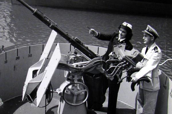 Ensign Mary F. Waters and Lt. Wm. J. Sweeny check a 20 mm canon at Bethlehem Hingham Shipyard in Massachusetts in 1944.