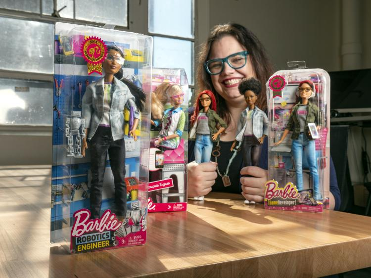 Information Science Assistant Professor Casey Fiesler poses with Robotics Engineer Barbie dolls.