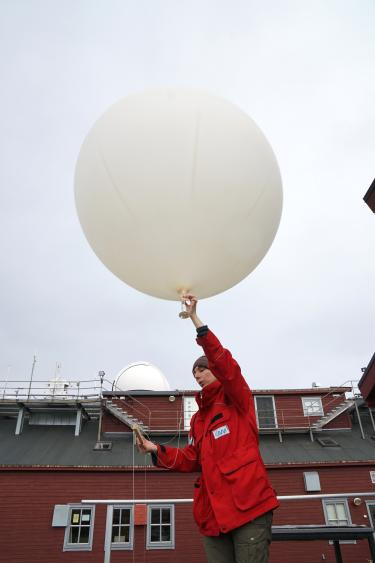 A scientist at a research facility in Ny-Älesund prepares to release a weather balloon.