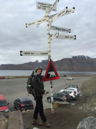 A pole in Longyearbyen is adorned with arrows pointing the way toward major cities far to the south – as well as a sign warning of polar bears.