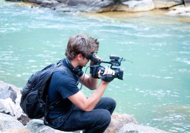 A student films the water.