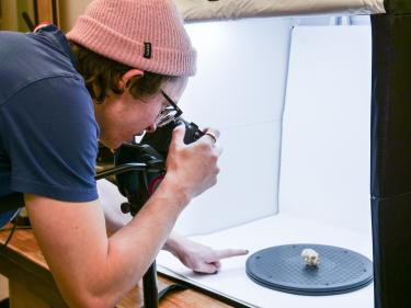 Student taking a photo of a fossil inside a light box.