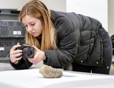 Student taking photo of fossil on the table.