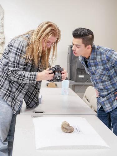 Students gathered around a camera reviewing a photo of fossil.