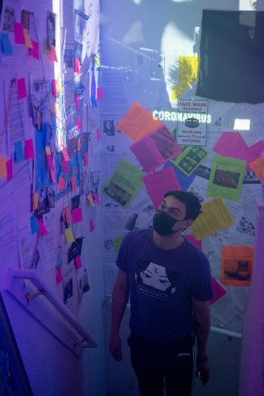 As you enter the ICA loop installation, you enter the information overload room. There are news articles hanging on the wall as well as news clips from the pandemic playing on repeat. This room represents how much information is out there and how much is misinformation.