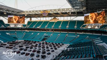 Cars parked inside of Hard Rock Stadium for a drive-in movie.
