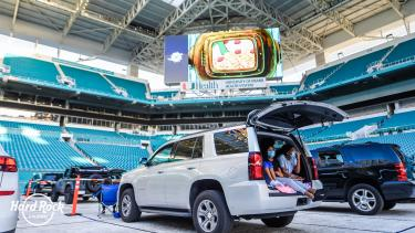People sitting in a car inside of Hard Rock Stadium with masks on for a drive-in movie.
