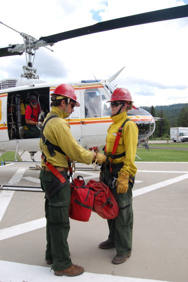 """Photo taken by Jody Jahn during dissertation fieldwork as she observes a """"buddy check"""" before a helicopter rappel near New Meadows, Idaho."""