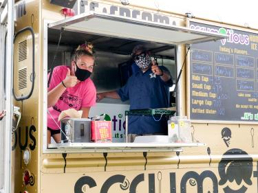 Scrumptious employees giving thumbs up inside the ice cream truck.