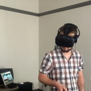 Student uses a virtual reality headset and handsets.