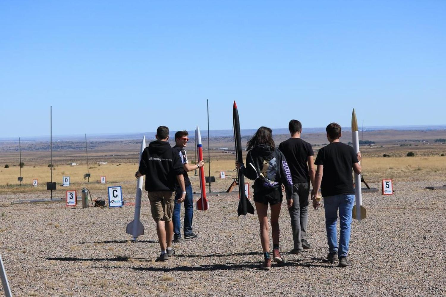 Several Sounding Rocket Lab team members prepare to launch their rockets.