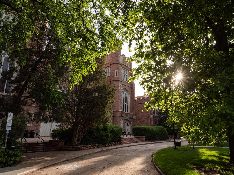 Sunlight peeks through the trees surrounding Macky Auditorium