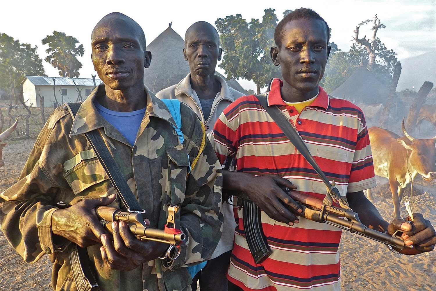 Local militia, two with AK-47s, guard the Duk Lost Boys Clinic compound located behind them
