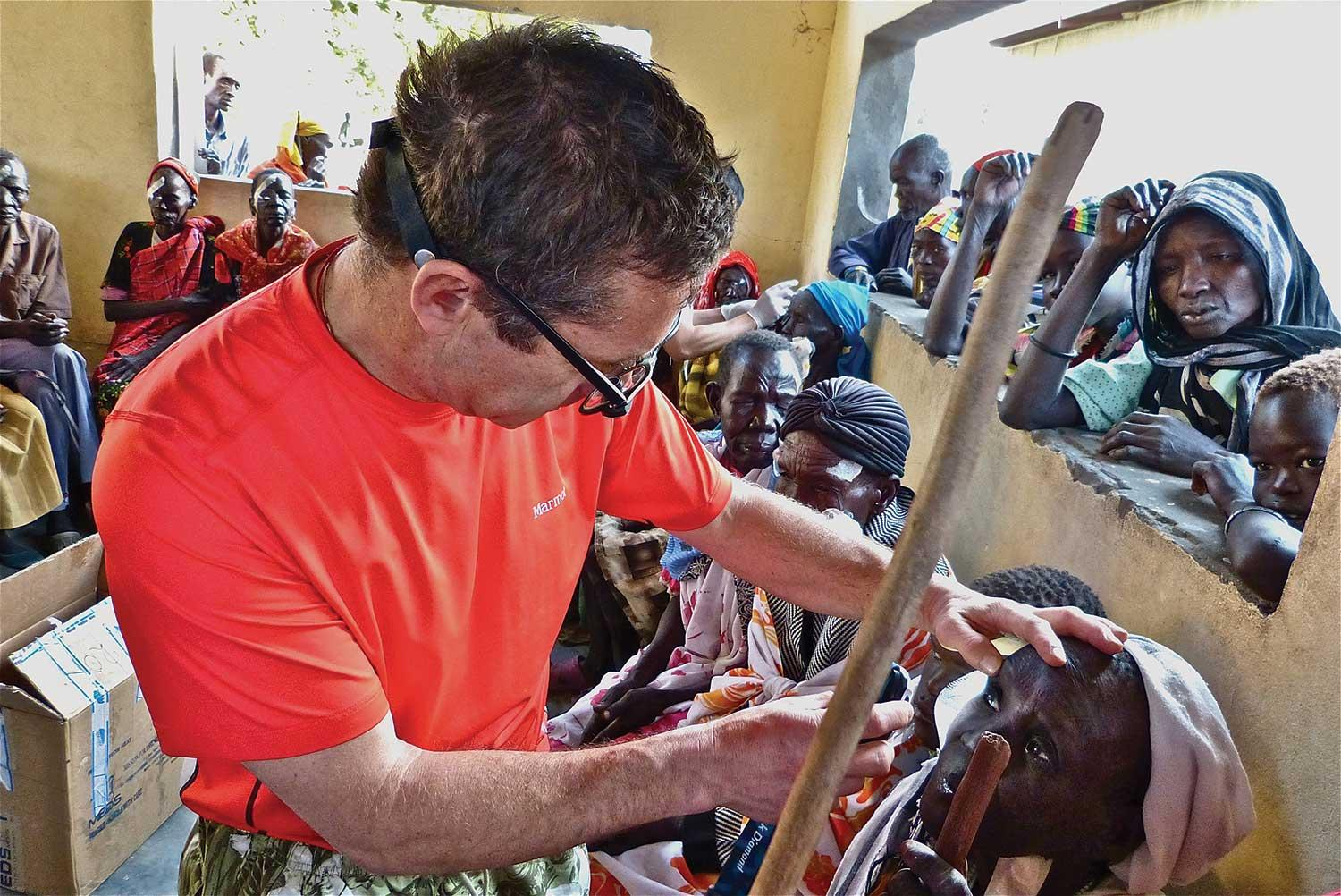 Dr. Geoff Tabin examines a woman after surgery in the clinic filled with patients and their families