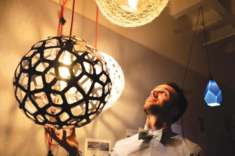 Nicholas Defaria looks at his lamps he created