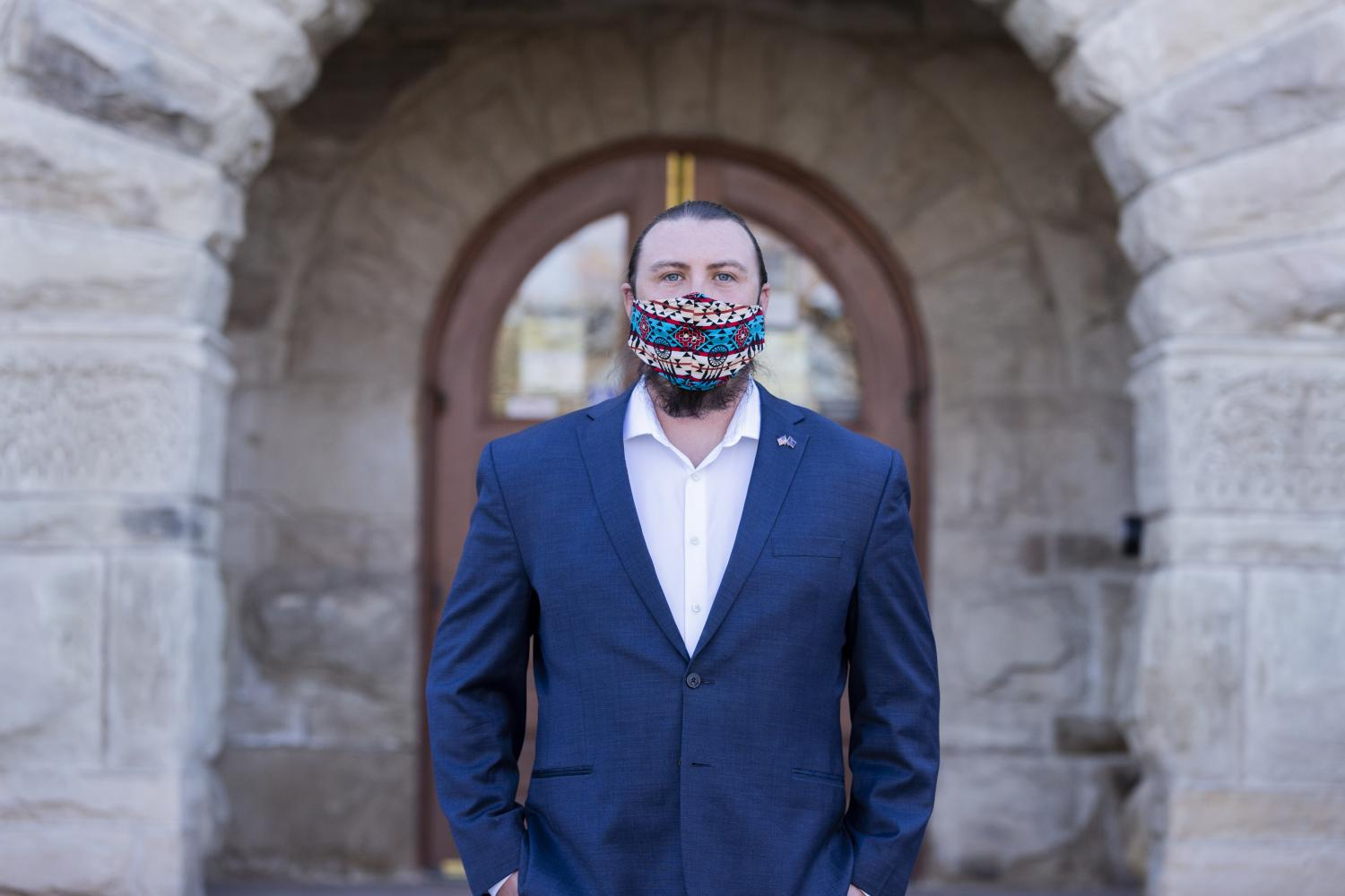 Carlton Quinn Shield Chief Gover standing in a suit and mask in front of a building on campus