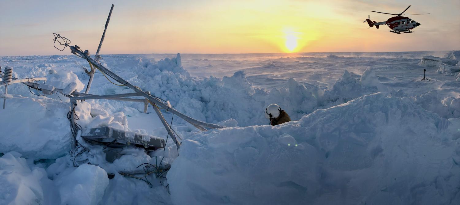 sunset and helicopter over researchers in the ice