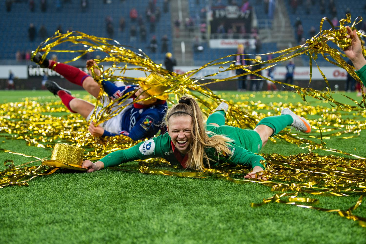 soccer goalie J.J. Tompkins celebrates on the field surrounded by gold streamers