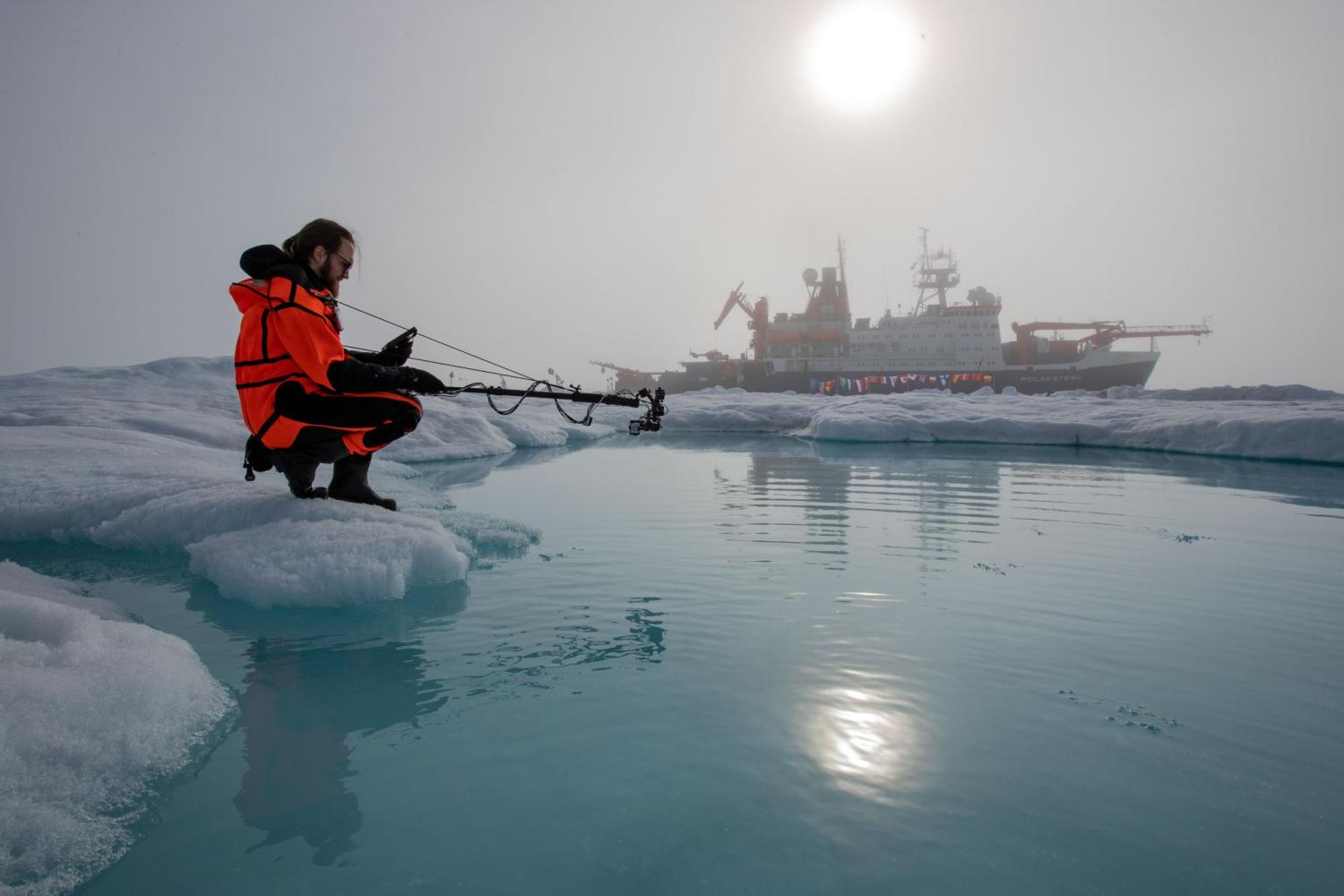 researcher crouched next to frozen water