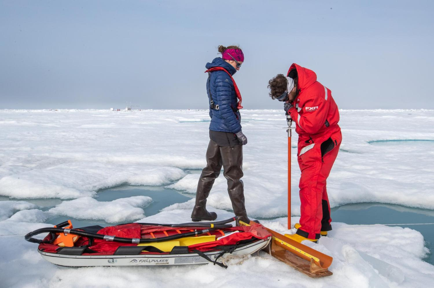two researchers obtaining an ice core