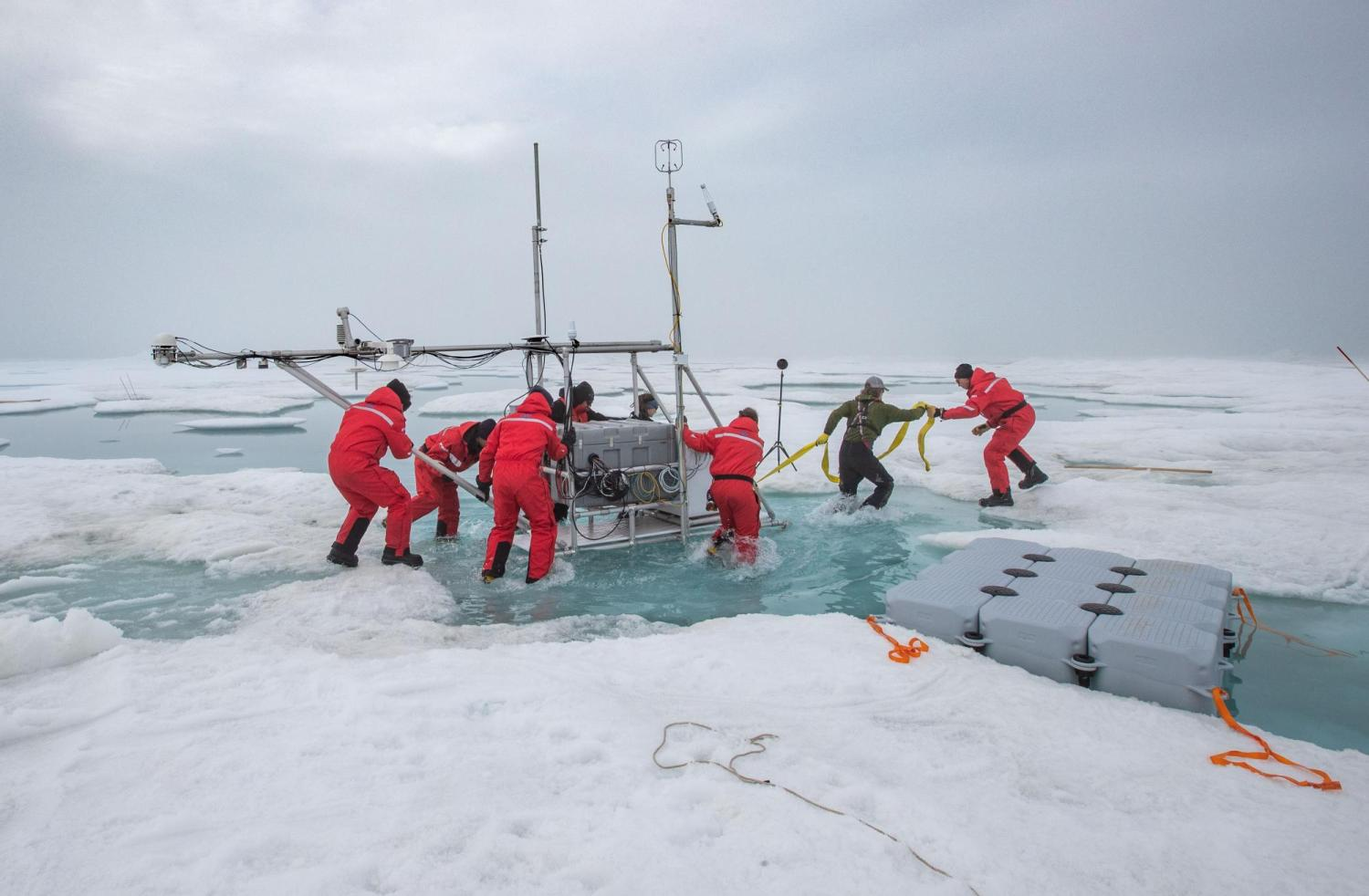 researchers pull scientific equipment from frozen water