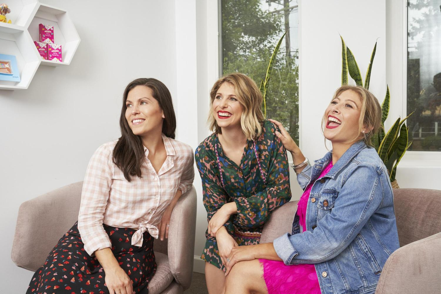 the three women co-presidents of the smarties candy company laugh and smile in their office