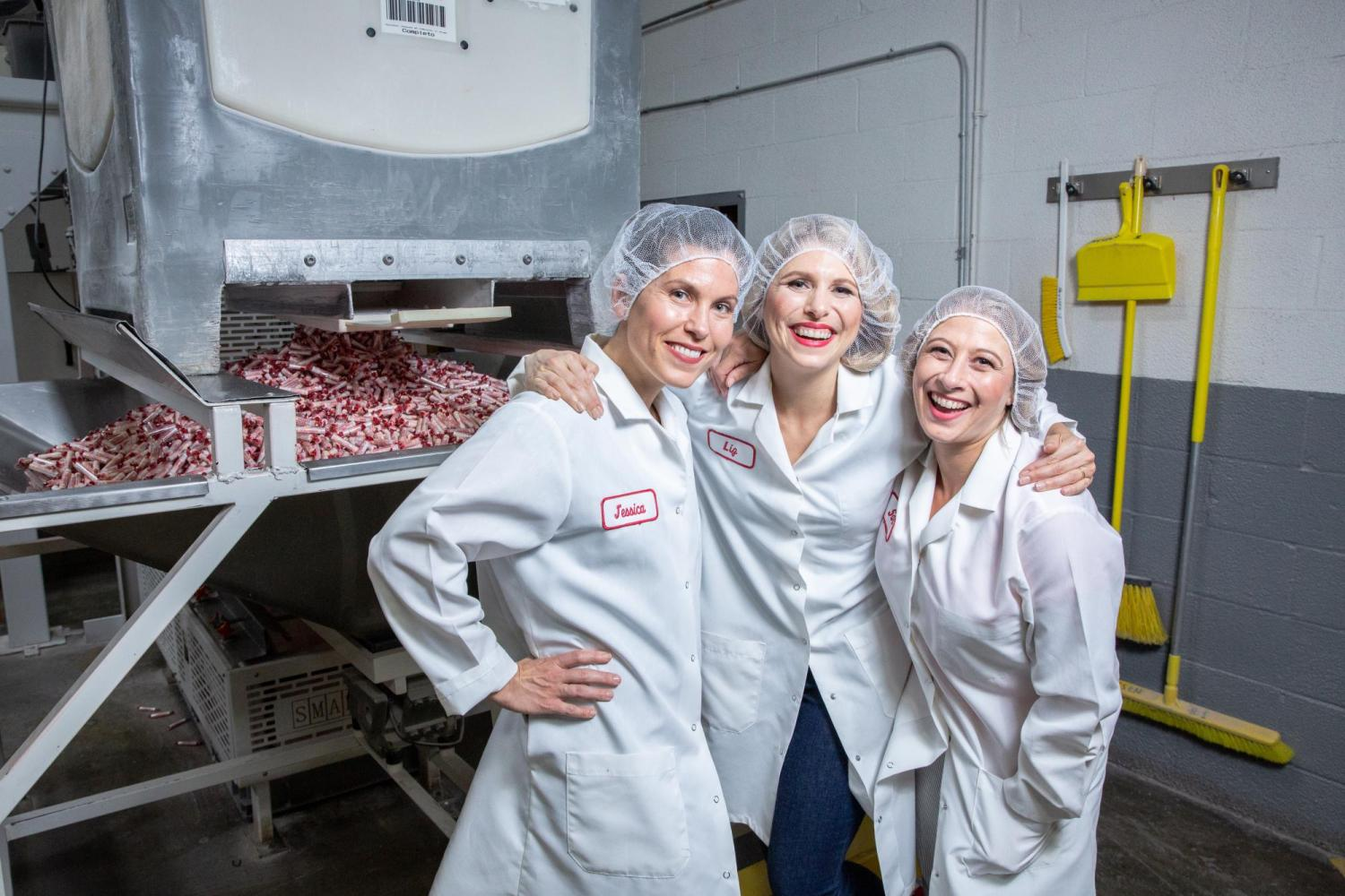 the three women co-presidents of the smarties candy company pose in the factory with hairnets