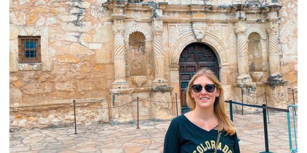 CU Boulder fan wearing a Buffs shirt in front of the Alamo
