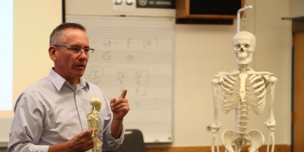 professor holding a skeleton