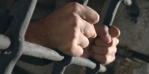 prisoner's hands on bars