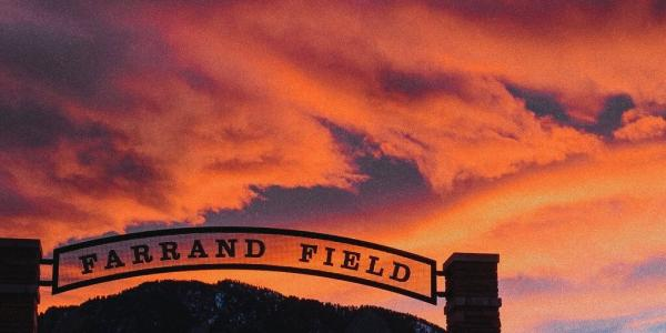 The sun sets over the arch of the entryway into Farrand Field.