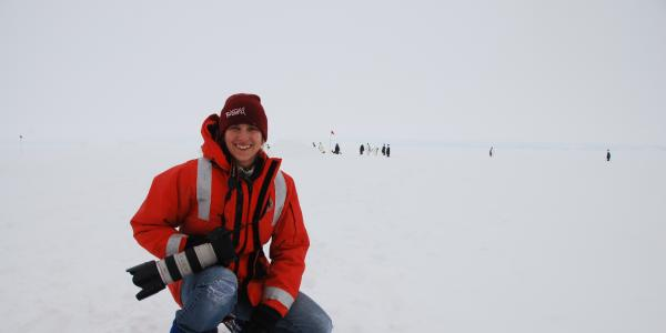 Cassandra Brooks kneeling on an icy terrain with a large camera in hand.