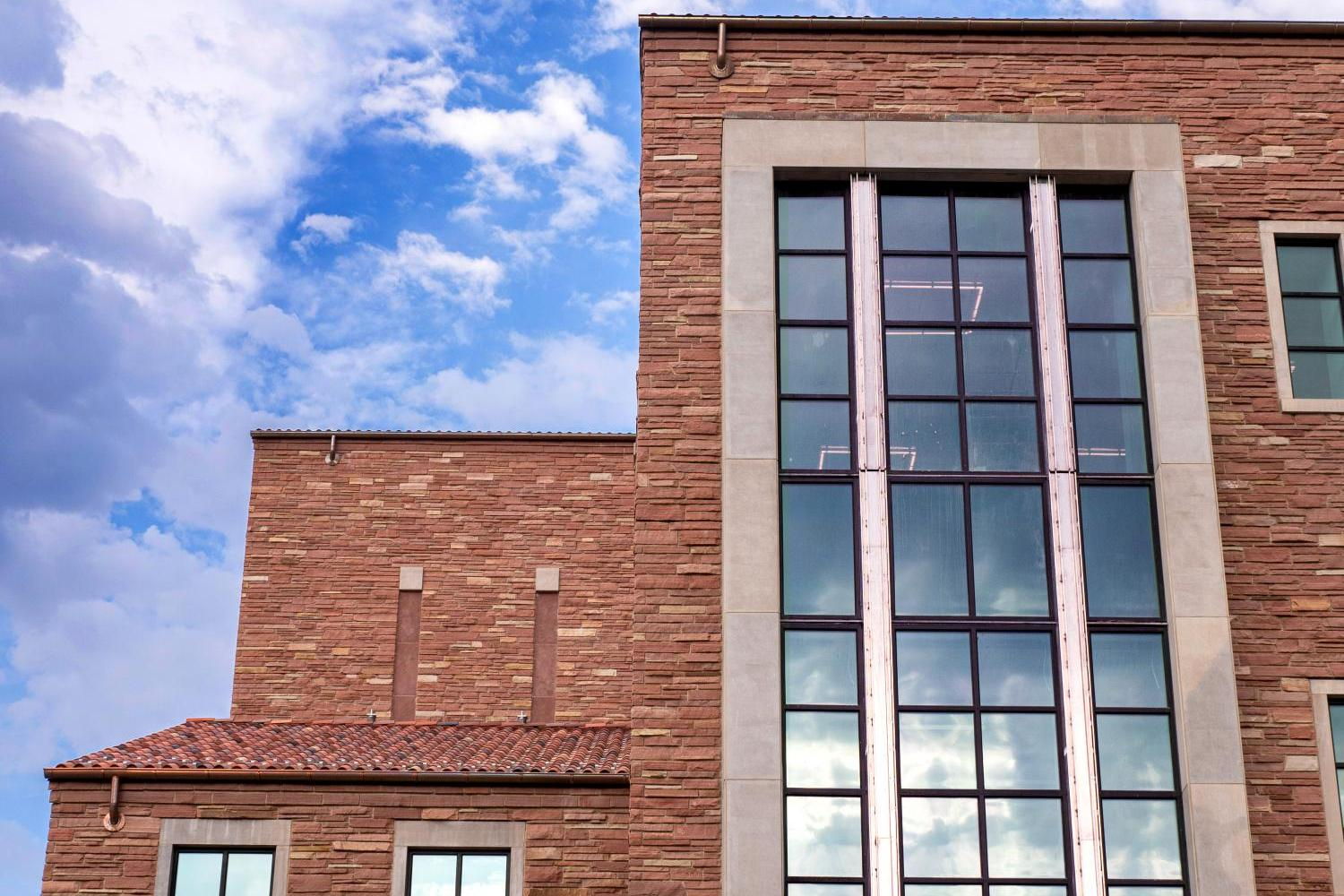 large window of the Imig Music Building against a blue sky