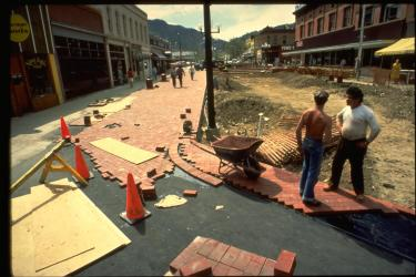Two men paving Pearl Street with bricks