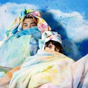 artists Alejandra Abad and Román Anaya sit in the colorful art flags they created
