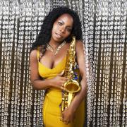 jazz musician Tia Fuller holds her saxophone while wearing a gold dress and standing in front of a sparkling beaded curtain