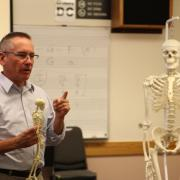 professor holding a skeleton