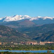 CU's campus stands out against the front range, Rocky mountains, and clear blue sky.