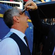 Former Broncos standout John Elway, right, helps Rick Reilly (Jour'81) get ready for Monday Night Football in October 2012.