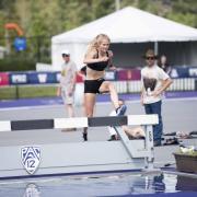 Val Constien jumps a hurdle.