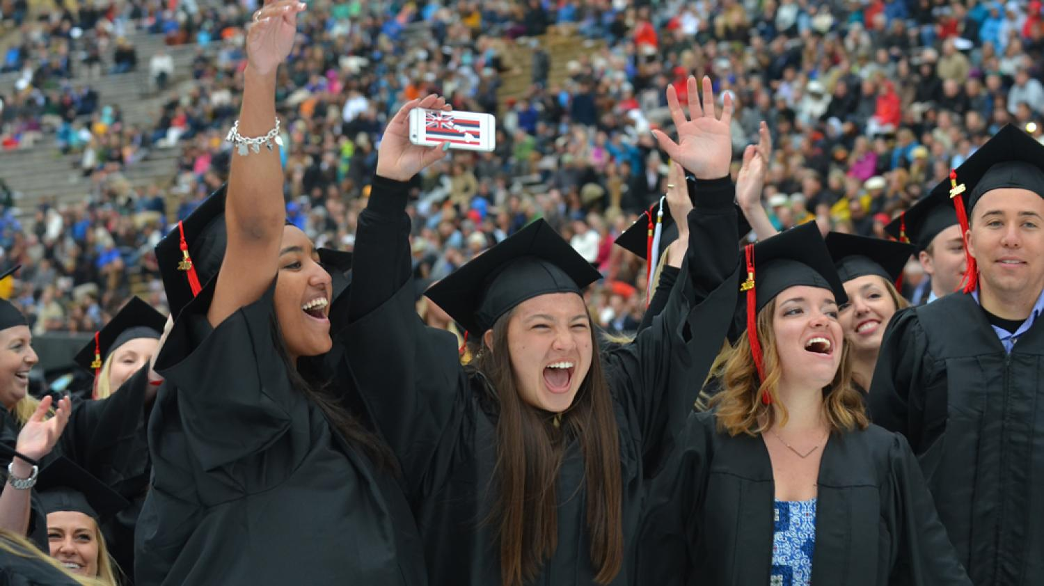 Graduates cheering at commencement ceremony