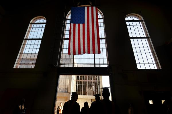 Graduates walk under American flag