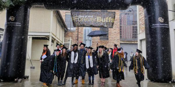 Graduates pose for a photo under Forever Buffs blow-up arch