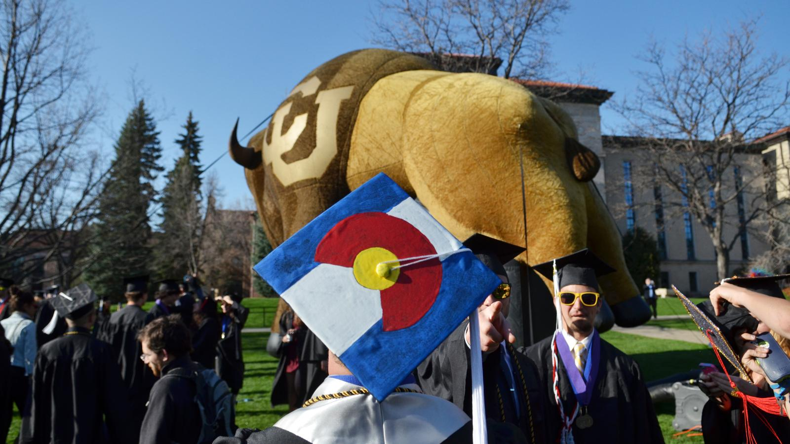 Graduate with CO State flag on mortar board in front of inflatable Alphie